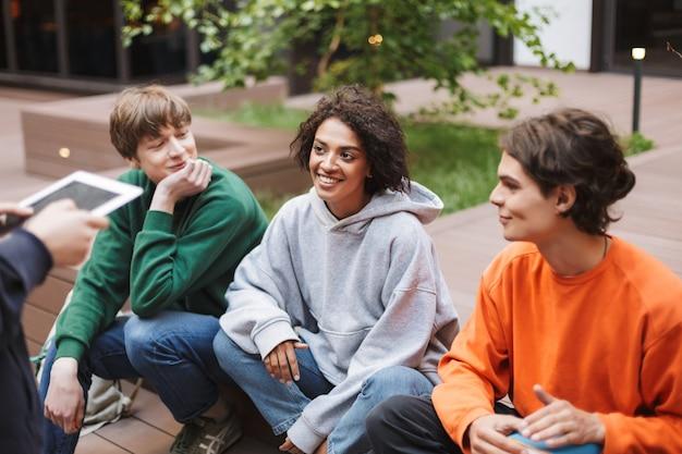 大学の中庭で友達と座っている暗い巻き毛の笑顔の女性。一緒に時間を過ごすクールな学生のグループ