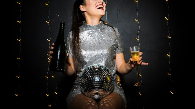 Smiling lady with disco ball, bottle and glass