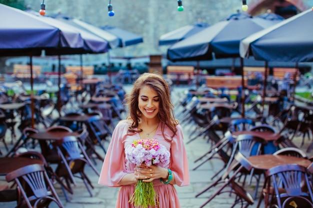 꽃 부케와 웃는 여자 c에서 외로운 테이블 가운데 서
