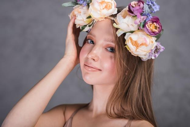頭の上の花を持つ女性の笑みを浮かべてください。