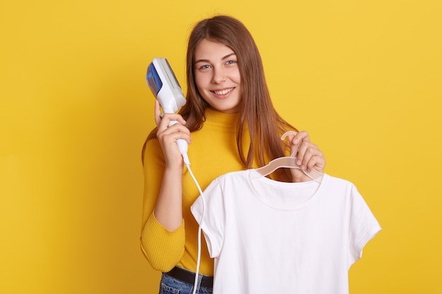 Smiling lady with hangers in hands, woman ironing her white t shirt with steam ironing