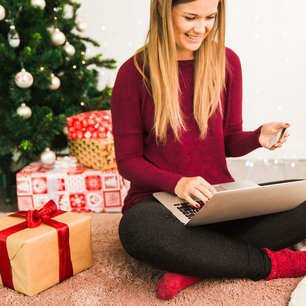 smiling-lady-with-laptop-and-plastic-card-near-gift-boxes-and-christmas-tree_23-2147973973.jpg