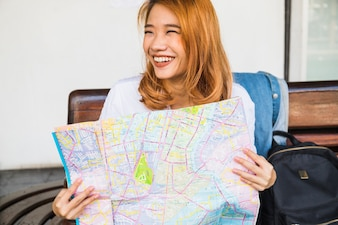 Smiling lady with map on bench
