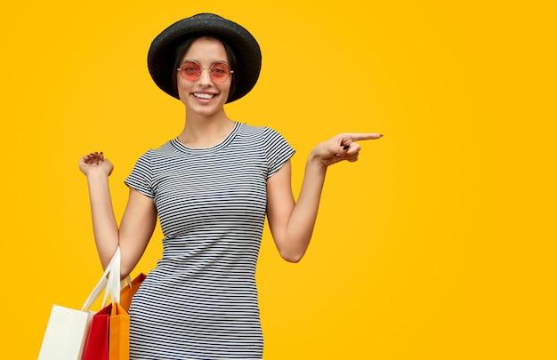 脇を指している紙袋で笑顔の女性