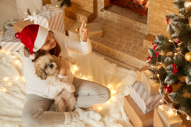 Smiling lady with pekingese dog in hands pointing finger up and showing something to her pet, female with crossed legs sitting on carpet near fireplace and hugging he puppy.
