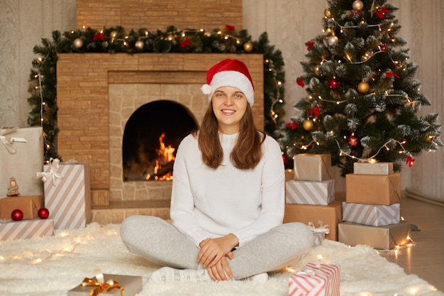 Smiling lady with positive emotions, female with toothy smile sitting with crossed legs, posing in living room with fireplace and christmas tree