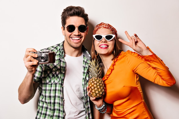 Smiling lady with red lipstick dressed in orange dress shows peace sign and holds pineapple. guy in sunglasses is smiling and making photos on retro camera.