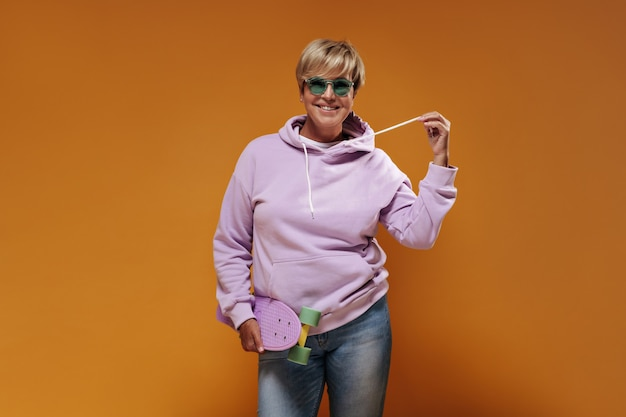 Smiling lady with short hair and modern glasses in pink sweatshirt and cool jeans posing with modern skateboard on orange backdrop.