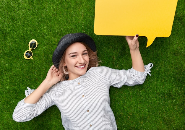 Smiling lady with speech balloon lying on lawn near sunglasses