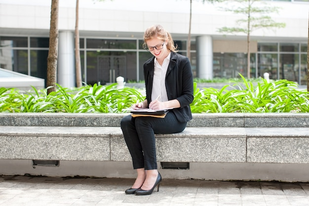 Smiling lady working and sitting on flowerbed