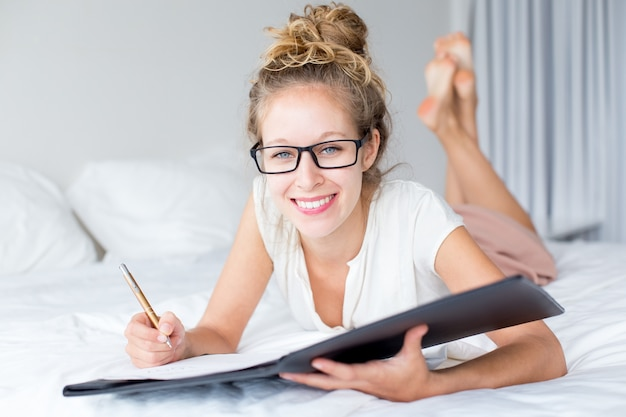 Smiling lady working with document on bed