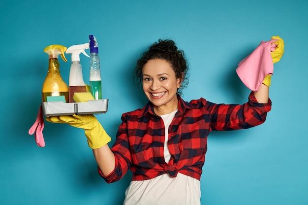 ピンクのぼろきれと化学洗浄剤でいっぱいのトレイで腕を上げる笑顔のラテンアメリカ人女性