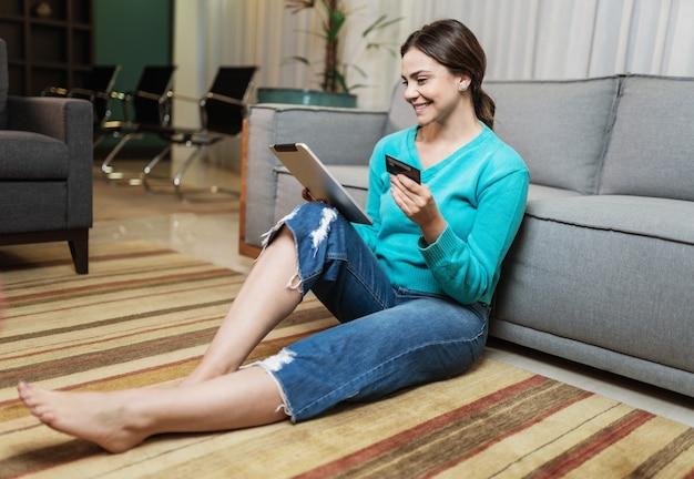 웃고 있는 라티나 여성 고객은 휴대전화 신용 은행 카드를 들고 온라인 쇼핑을 합니다.