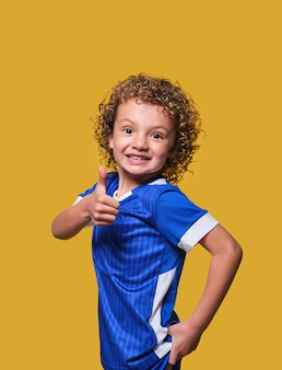Smiling latino boy soccer lover looks at camera with thumbs up on isolated wall