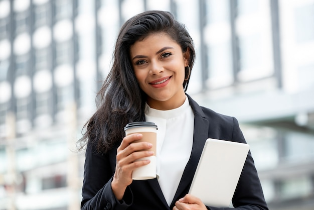Smiling latino business woman holding coffee cup and tablet computer