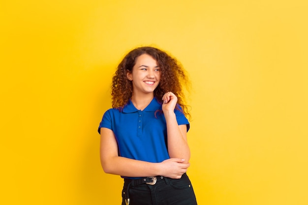 Smiling, laughting. caucasian teen's girl portrait on yellow studio background. beautiful female curly model in blue shirt. concept of human emotions, facial expression, sales, ad. copyspace.