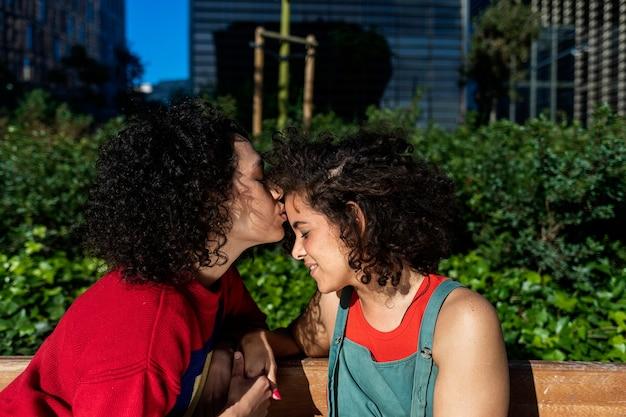 Улыбающаяся лесбийская пара обнимается и отдыхает на скамейке в парке