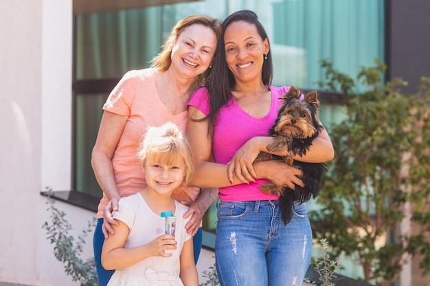 Улыбаясь лесбийская пара с ребенком и домашним щенком. лесбийская пара с приемной дочерью, концепция усыновления.