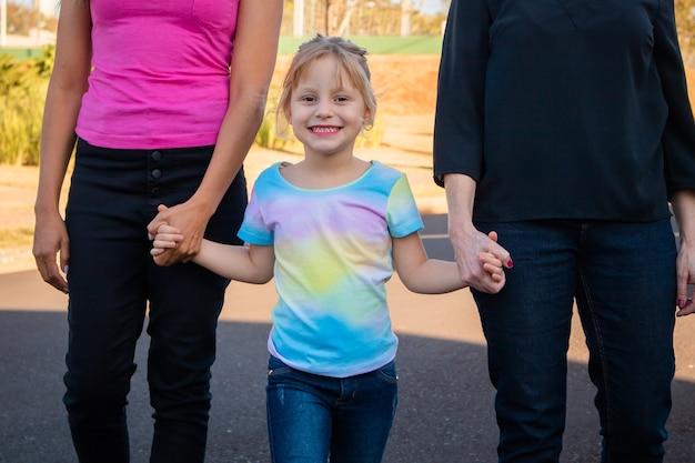Улыбаясь лесбийская пара с ребенком на фоне парка. лесбийская пара, держащая приемную дочь за руку, концепция усыновления