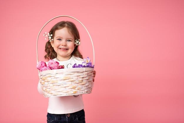 Улыбающаяся маленькая девочка держит в руках плетеную корзину из нежных белых, розовых и фиолетовых цветов
