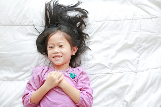 Smiling little asian child girl lying on bed looking at camera. above view.