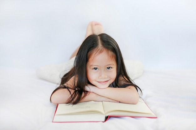 Smiling little asian child girl with hardcover book lying on bed and looking camera over white background.