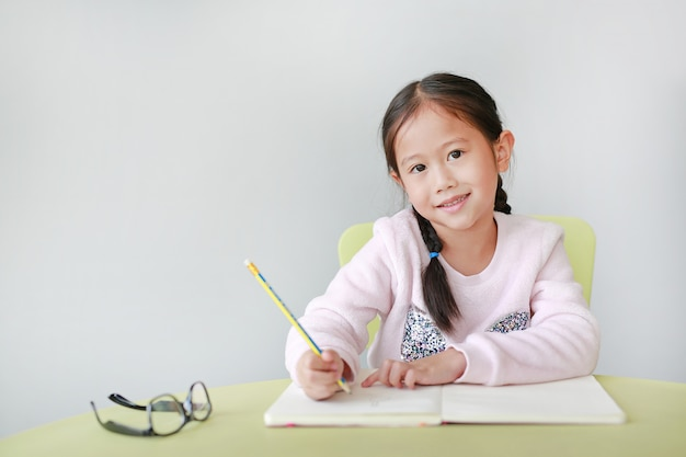 Smiling little asian child girl writes in a book or notebook with pencil on table in classroom.