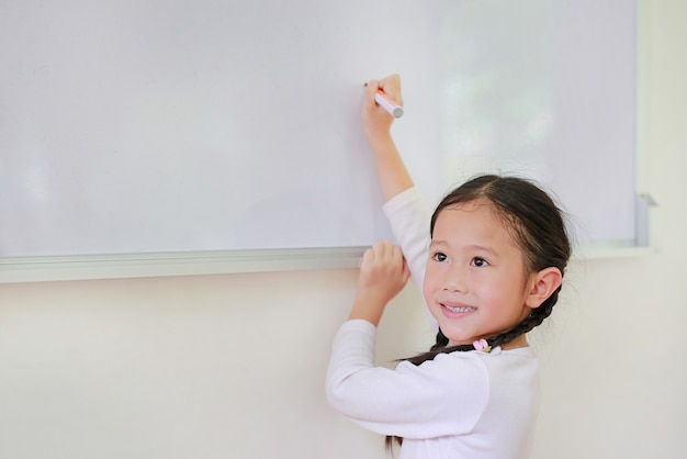 Smiling little asian child girl writing something on whiteboard with a marker