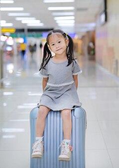 スーツケースに座って空港で小さなアジアの女の子を笑って。