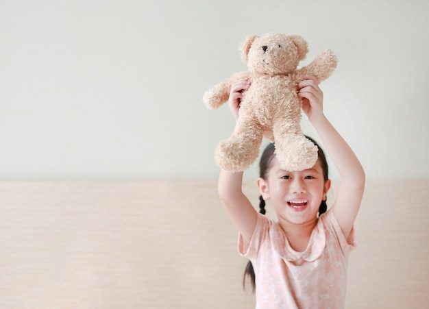 Smiling little asian girl raised up stuffed teddy bear while sitting on the bed at home.
