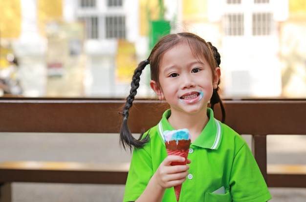 Smiling little asian kid girl enjoy eating ice cream cone with stains around her mouth.