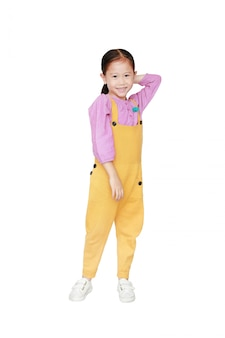 Smiling little asian kid girl in pink-yellow dungarees poses touched hair keep