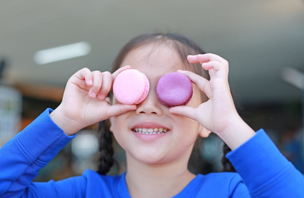 Smiling little asian kid girl playing and holding macaroons on her eyes.