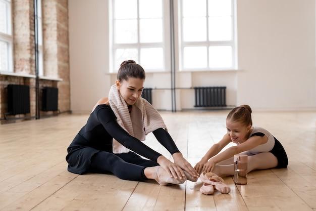 彼らが床に座ってダンススクールでバレエダンスの後に休んでいる間、彼女のトレーナーと話している小さなバレリーナの笑顔