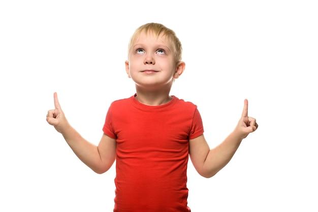 Улыбающийся маленький белокурый мальчик в красной футболке стоит и показывает указательными пальцами вверх