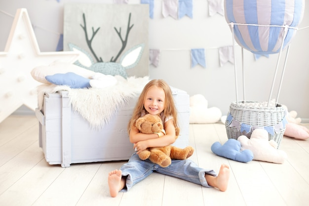 Smiling little blond girl hugs a teddy bear on the wall of a decorative balloon. the child plays in the children's room with toys. the concept of childhood, travel. birthday, holiday decorations
