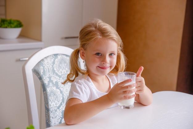 Smiling little blonde girl drinking milk in the kitchen