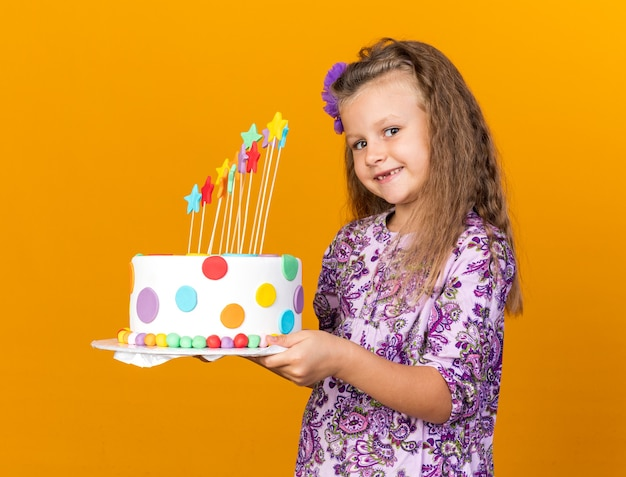 Smiling little blonde girl holding birthday cake isolated on orange wall with copy space