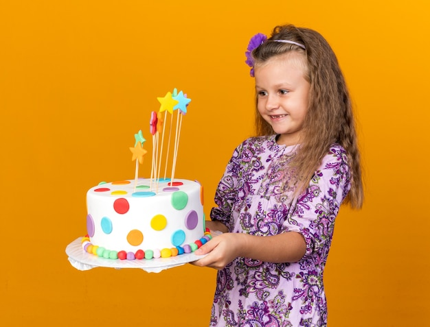 Smiling little blonde girl holding and looking at birthday cake isolated on orange wall with copy space
