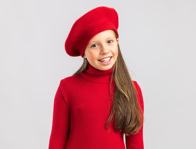 Smiling little blonde girl wearing red beret looking at front isolated on white wall with copy space