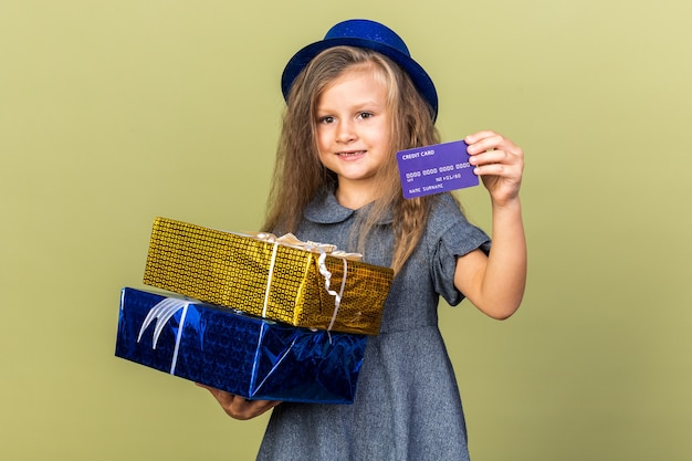 Smiling little blonde girl with blue party hat holding gift boxes and credit card isolated on olive green wall with copy space