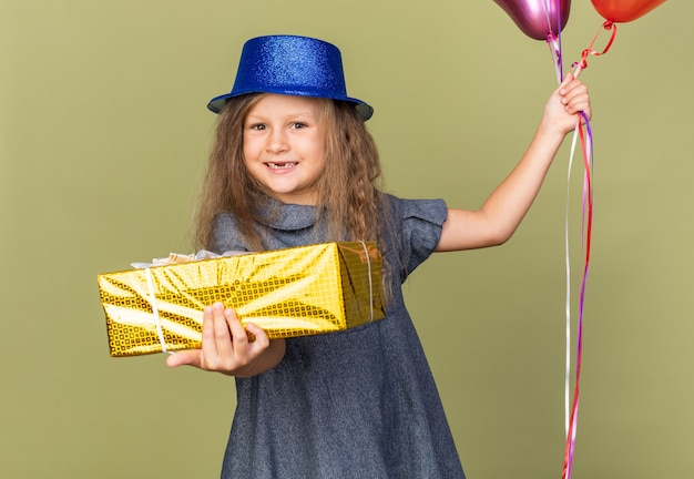 Smiling little blonde girl with blue party hat holding helium balloons and gift box isolated on olive green wall with copy space