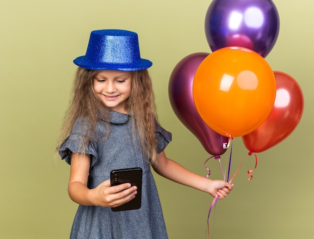 Smiling little blonde girl with blue party hat holding helium balloons and looking at phone isolated on olive green wall with copy space