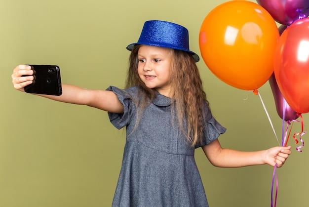 Sorridente bambina bionda con cappello da festa blu che tiene palloncini di elio e telefono che prende selfie isolato su parete verde oliva con spazio di copia