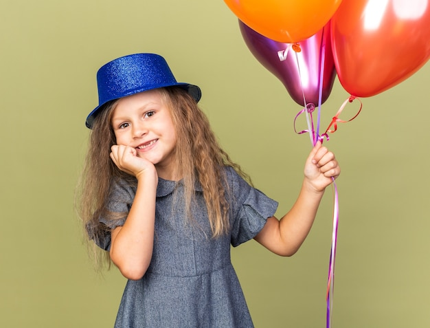 Smiling little blonde girl with blue party hat holding helium balloons and putting hand on chin isolated on olive green wall with copy space