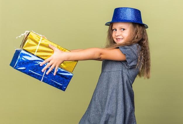 Sorridente bambina bionda con cappello da festa blu in piedi lateralmente tenendo scatole regalo isolate su parete verde oliva con spazio di copia