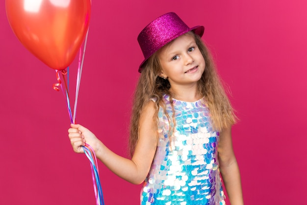 Smiling little blonde girl with purple party hat holding helium balloons and looking  isolated on pink wall with copy space