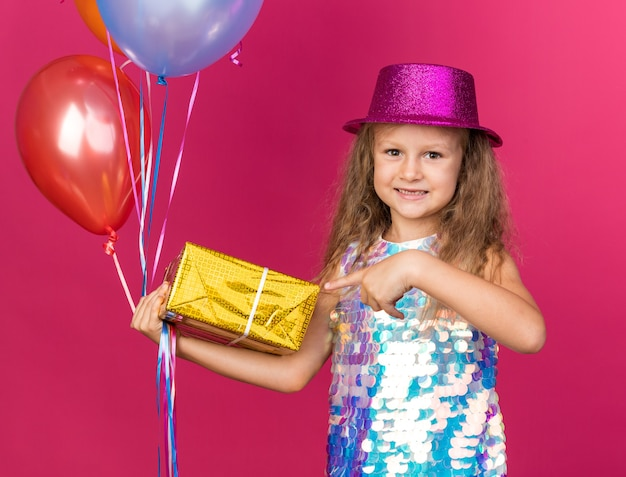 Smiling little blonde girl with purple party hat holding helium balloons and pointing at gift box isolated on pink wall with copy space