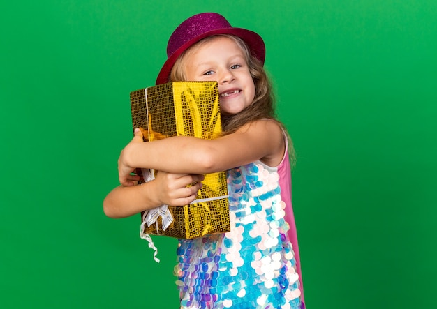 Smiling little blonde girl with purple party hat hugging gift box isolated on green wall with copy space