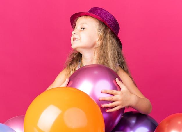 Sorridente bambina bionda con cappello viola partito in piedi con palloncini di elio guardando lato isolato sul muro rosa con spazio di copia